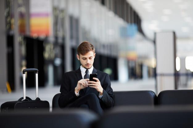 Un hombre conectado a su teléfono trabajando en un aeropuerto